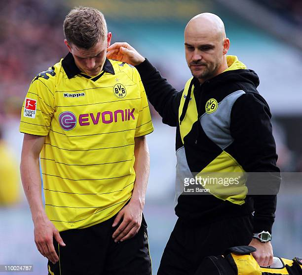 Sven Bender of Dortmund leaves injured the pitch during the Bundesliga match between 1899 Hoffenheim and Borussia Dortmund at RheinNeckar Arena on...