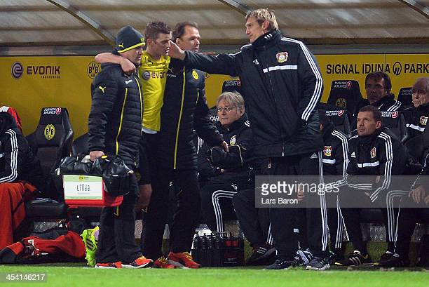 Sven Bender of Dortmund leaves injured the pitch next to head coach Sami Hyypiae of Leverkusen during the Bundesliga match between Borussia Dortmund...