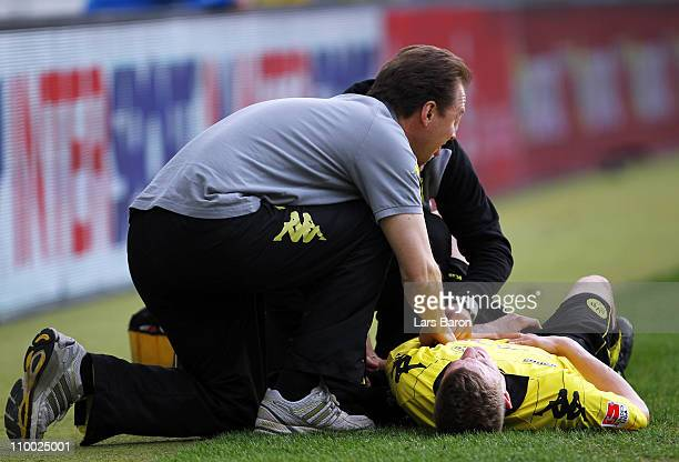 Sven Bender of Dortmund lies injured on the pitch during the Bundesliga match between 1899 Hoffenheim and Borussia Dortmund at RheinNeckar Arena on...
