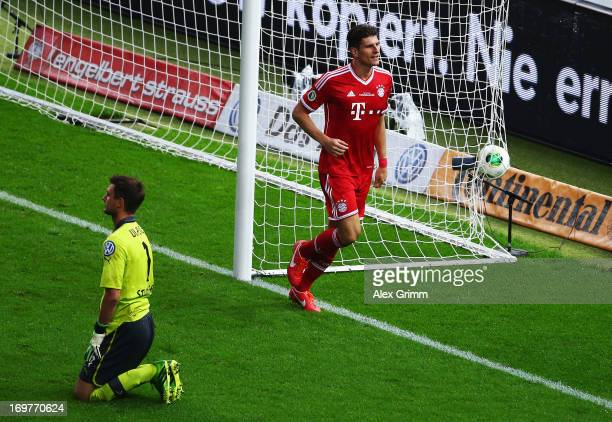 Sven Ulreich of VfB Stuttgart looks dejected as Mario Gomez of Bayern Muenchen celebrates scoring their second goal during the DFB Cup Final match...