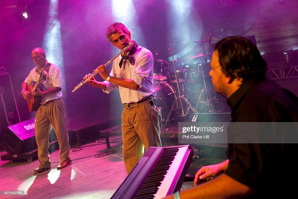 Sveral Brazilian Gaucho men in traditional dress playing flute guiatr and keyboards as a band on stage Reponte da Cancao music festival and song...