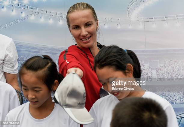 Svetlana Kuznetsova of Russia offers a cap to a kid at the MercedesBenz Kids event during day 1 of the 2017 China Open at the China National Tennis...