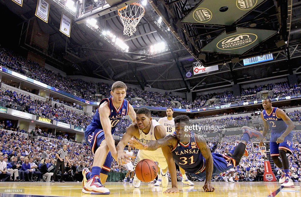 Sviatoslav Mykhailiuk #10 and Jamari Traylor #31 of the the Kansas Jayhwaks and Karl-Anthony Towns #12 of the Kentucky Wildcats battle for a loose ball during the game against in the State Farm Champions Classic at Bankers Life Fieldhouse on November 18, 2014 in Indianapolis, Indiana.