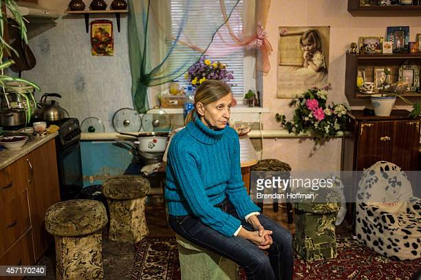 Svitlana Kostromina sits in the kitchen at the home where she her daughter and her granddaughter are living with a family in their church's...