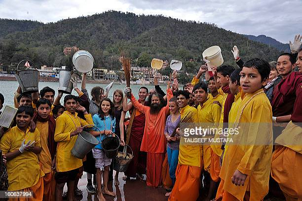 Swami Chidanand Saraswatiji president and spiritual head of the Parmarth Niketam Ashram poses with international yoga practitioners on the banks of...