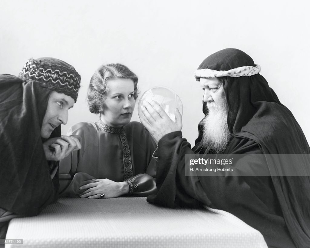 Swami looking into crystal ball, with woman and man watching intently. : Bildbanksbilder