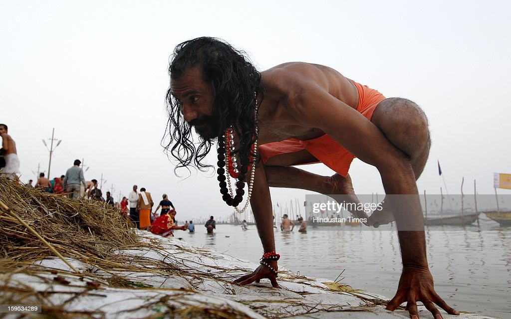 Swami Omkar Nand Saraswati performs yoga at the bank of Sangam confluence of river Ganga, Yamnuna and mythical Saraswati on the occasion of Makar Sankranti on January 15, 2013 in Allahabad, India. Kumbh is World's biggest religious gathering, in which more than 100 million of Hindus and sikh devotees will take part over next 55 days. Apart from being pilgrimage of faith, salvation and hope for millions of devotees, it also serve as meeting ground for the vast spectrum of Indian religious and spiritual views.