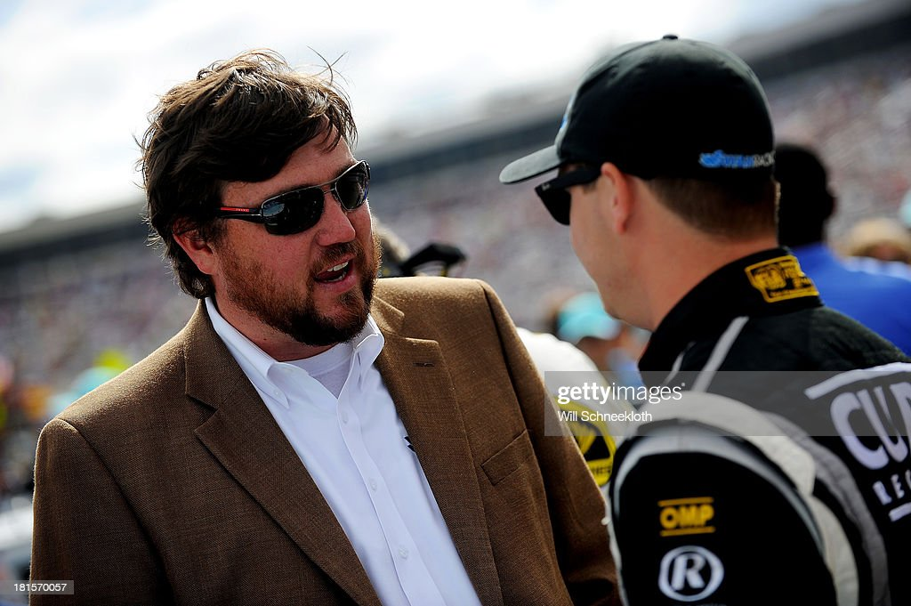 Swan Racing team owner Brandon Davis talks with Kevin Swindell, driver of the #30 Genny Light Toyota, during the NASCAR Sprint Cup Series Sylvania 300 at New Hampshire Motor Speedway on September 22, 2013 in Loudon, New Hampshire.
