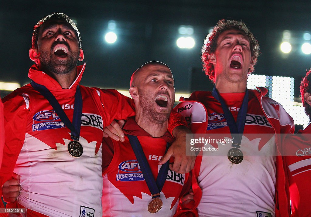Swans co-captains Jarrad McVeigh and Adam Goodes sing the team song as they are presented to the crowd after winning the 2012 AFL Grand Final match between the Sydney Swans and the Hawthorn Hawks at Melbourne Cricket Ground on September 29, 2012 in Melbourne, Australia.