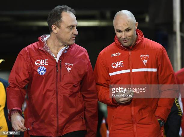Swans head coach John Longmire and Tom Harley walk out of the rooms during the round 15 AFL match between the Melbourne Demons and the Sydney Swans...