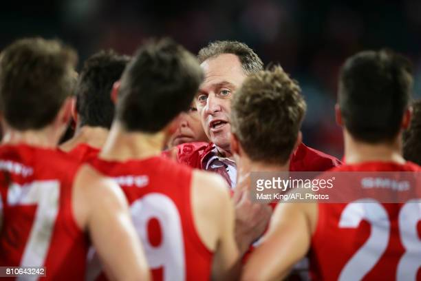 Swans head coach John Longmire speaks to players at three quarter time during the round 16 AFL match between the Sydney Swans and the Gold Coast Suns...
