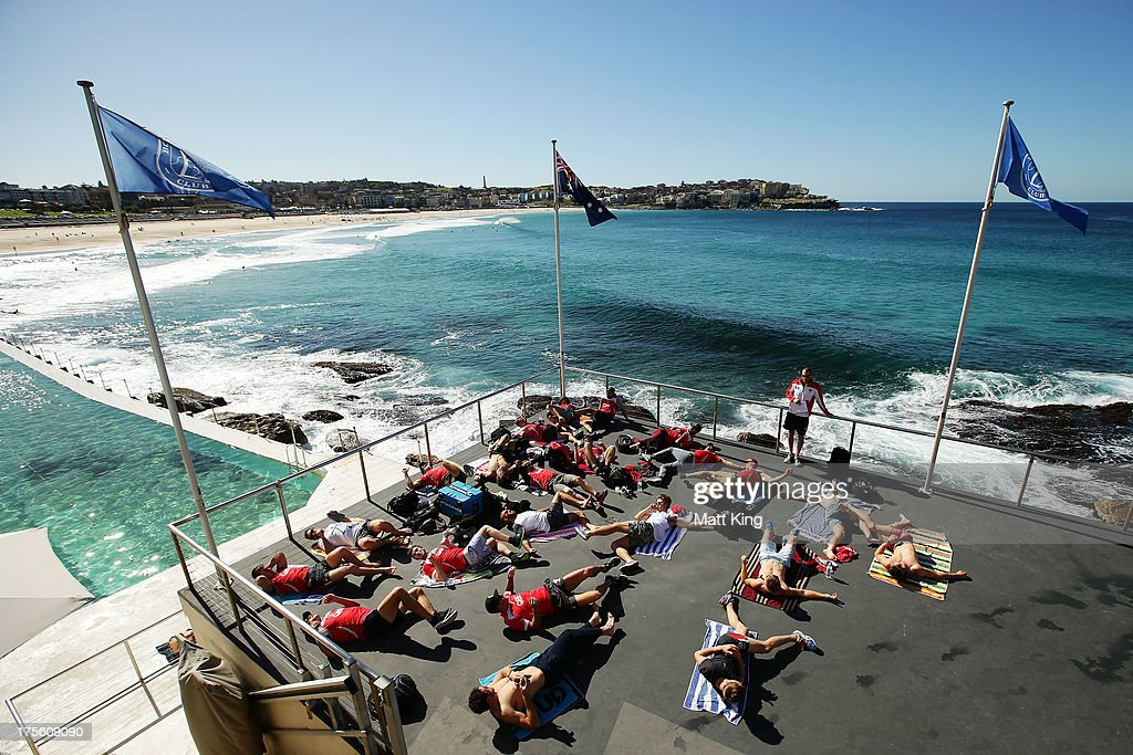 Swans players stretch during a Sydney Swans AFL recovery session at Bondi Icebergs Pool on August 5, 2013 in Sydney, Australia.