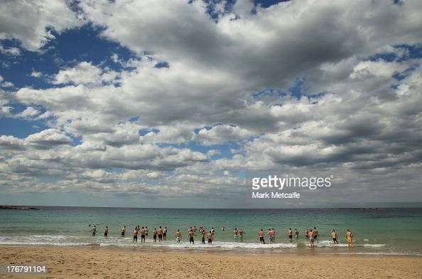 Swans players wade in the ocean during a during a Sydney Swans AFL recovery session at Coogee Beach on August 19 2013 in Sydney Australia