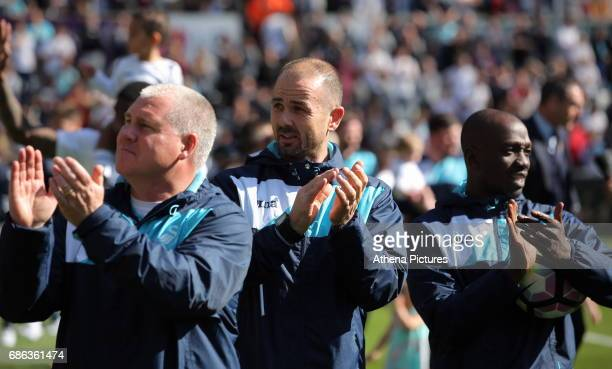 Swansea assistant coaches Nigel Gibbs Karl Halabi and Claude Makelele thank home supporters after the Premier League match between Swansea City and...