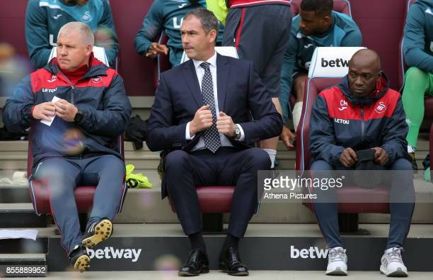 Swansea City Assistant manager Nigel Gibbs Swansea manager Paul Clement and Swansea assistant coach Claude Makelele sit on the bench during the...