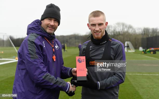 Swansea City manager Paul Clement presents player Oliver McBurnie with his Premier League 2 award with team mates at Swansea City's training ground...