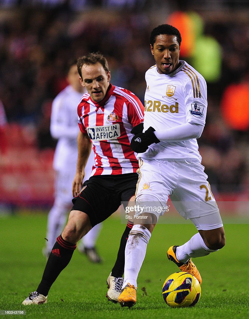 Swansea City player Jonathan De Guzman is challenged by Sunderland player David Vaughan during the Barclays Premier League match between Sunderland and Swansea City at Stadium of Light on January 29, 2013 in Sunderland, England.