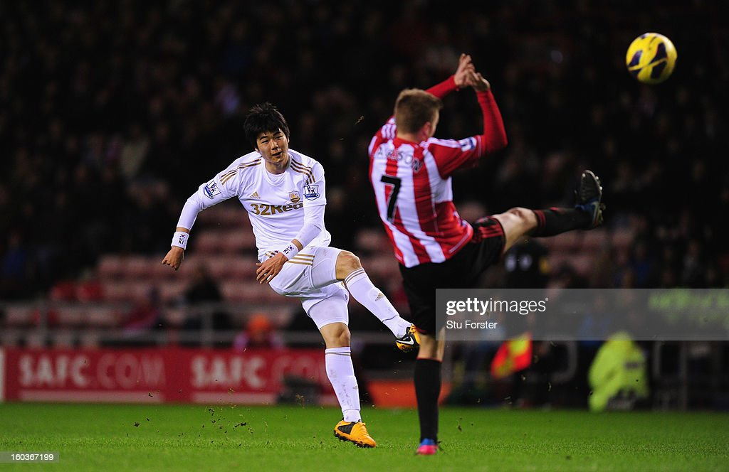 Swansea City player Ki Sung-Yeung (l) lets fly from outside the box during the Barclays Premier League match between Sunderland and Swansea City at Stadium of Light on January 29, 2013 in Sunderland, England.