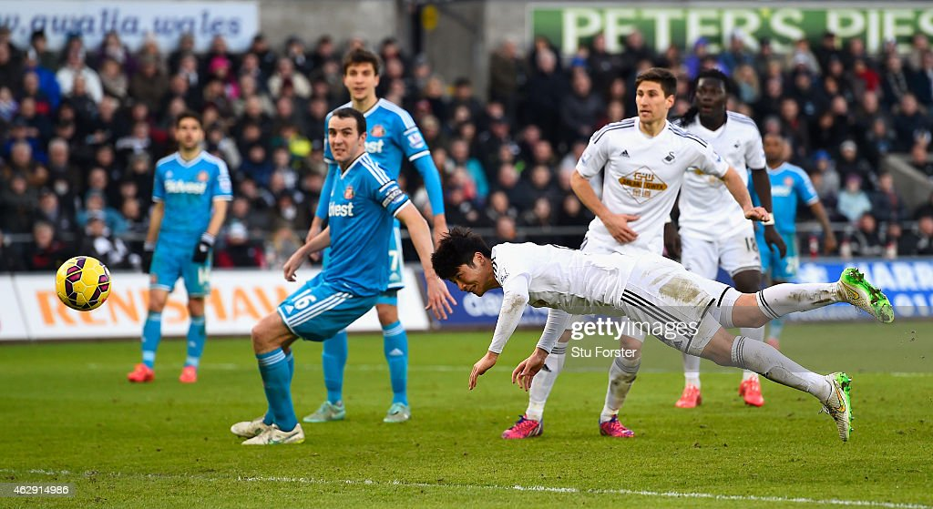 Swansea City player Ki SungYueng dives to head the first Swansea goal during the Barclays Premier League match between Swansea City and Sunderland at...