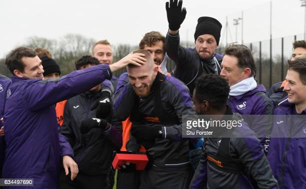 Swansea City player Oliver McBurnie with his Premier League 2 award is congratulated by team mates at Swansea City's training ground at Fairwood on...