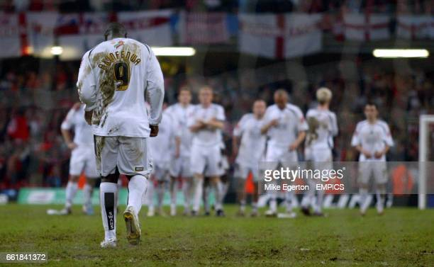 Swansea City's Adebayo Akinfenwa trudges back to his team mates after missing a penalty