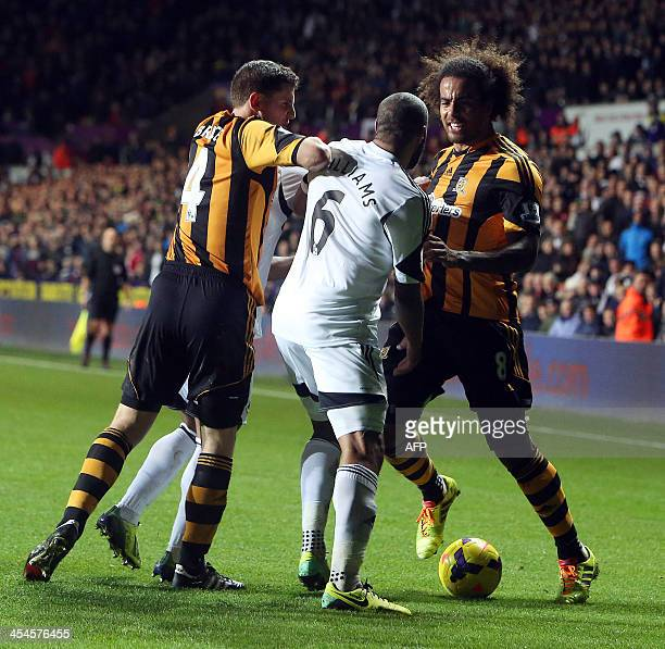 Swansea City's Britishborn Welsh defender Ashley Williams scuffles with Hull City's Britishborn Northern Irish defender Alex Bruce during a Premier...