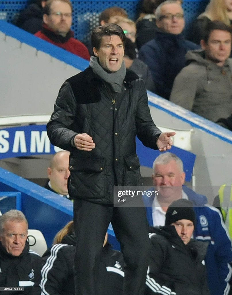 Swansea City's Danish manager Michael Laudrup gestures during the English Premier League football match between Chelsea and Swansea City at Stamford Bridge in London on December 26, 2013. Chelsea won the game 1-0. USE. No use with unauthorized audio, video, data, fixture lists, club/league logos or live services. Online in-match use limited to 45 images, no video emulation. No use in betting, games or single club/league/player publications.