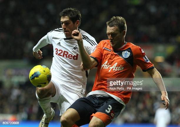 Swansea City's Danny Graham and Queens Park Rangers' Clint Hill battle for the ball