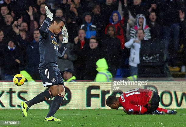 Swansea City's Dutch goalkeeper Michel Vorm gestures after challenging Cardiff City's English striker Fraizer Campbell outside the box for which he...