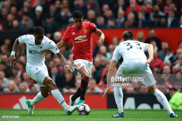 Swansea City's Dutch midfielder Leroy Fer and Swansea City's Argentinian defender Federico Fernandez challenge Manchester United's English striker...