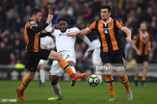 Swansea City's Dutch midfielder Leroy Fer vies with Hull City's Scottish defender Andrew Robertson and Hull City's English defender Harry Maguire...