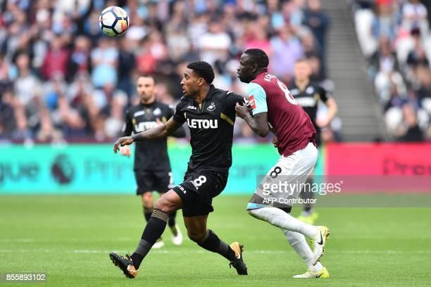 Swansea City's Dutch midfielder Leroy Fer vies with West Ham United's Senegalese midfielder Cheikhou Kouyate during the English Premier League...