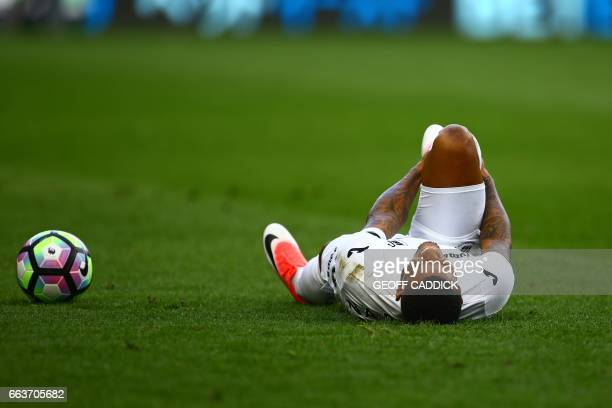 Swansea City's Dutch midfielder Luciano Narsingh reacts on the floor after picking up an injury during the English Premier League football match...