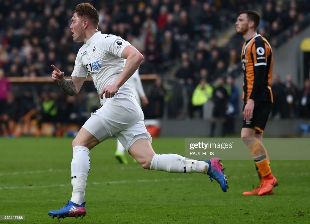 Swansea City's English defender Alfie Mawson (L) celebrates scoring their late goal during the English Premier League football match between Hull City and Swansea City at the KCOM Stadium in Kingston upon Hull, north east England on March 11, 2017. Niasse scored both goals as Hull won the game 2-1. / AFP PHOTO / Paul ELLIS / RESTRICTED TO EDITORIAL USE. No use with unauthorized audio, video, data, fixture lists, club/league logos or 'live' services. Online in-match use limited to 75 images, no video emulation. No use in betting, games or single club/league/player publications. /