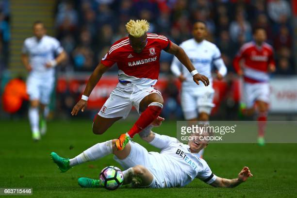 TOPSHOT Swansea City's English defender Alfie Mawson is booked for this challenge on Middlesbrough's Spanish midfielder Adama Traore during the...