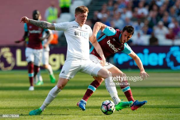 Swansea City's English defender Alfie Mawson vies with West Ham United's Argentinian striker Jonathan Calleri during the English Premier League...