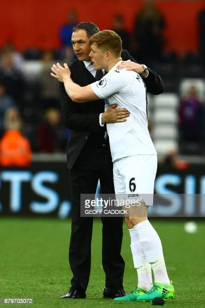 Swansea City's English head coach Paul Clement celebrates with Swansea City's English defender Alfie Mawson on the pitch after the English Premier...