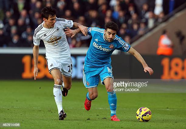 Swansea City's English midfielder Jack Cork and Sunderland's Spanish midfielder Jordi Gomez vie for the ball during the English Premier League...