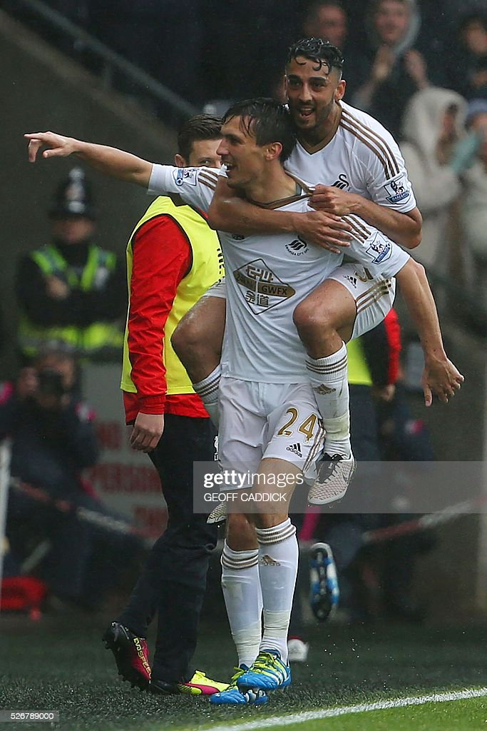 Swansea City's English midfielder Jack Cork (L) celebrates after scoring their second goal with Swansea City's Welsh defender Neil Taylor (behind) during the English Premier League football match between Swansea City and Liverpool FC at the Liberty Stadium, in Swansea, South Wales, on May 1, 2016. / AFP / GEOFF CADDICK / RESTRICTED TO EDITORIAL USE. No use with unauthorized audio, video, data, fixture lists, club/league logos or 'live' services. Online in-match use limited to 75 images, no video emulation. No use in betting, games or single club/league/player publications. /