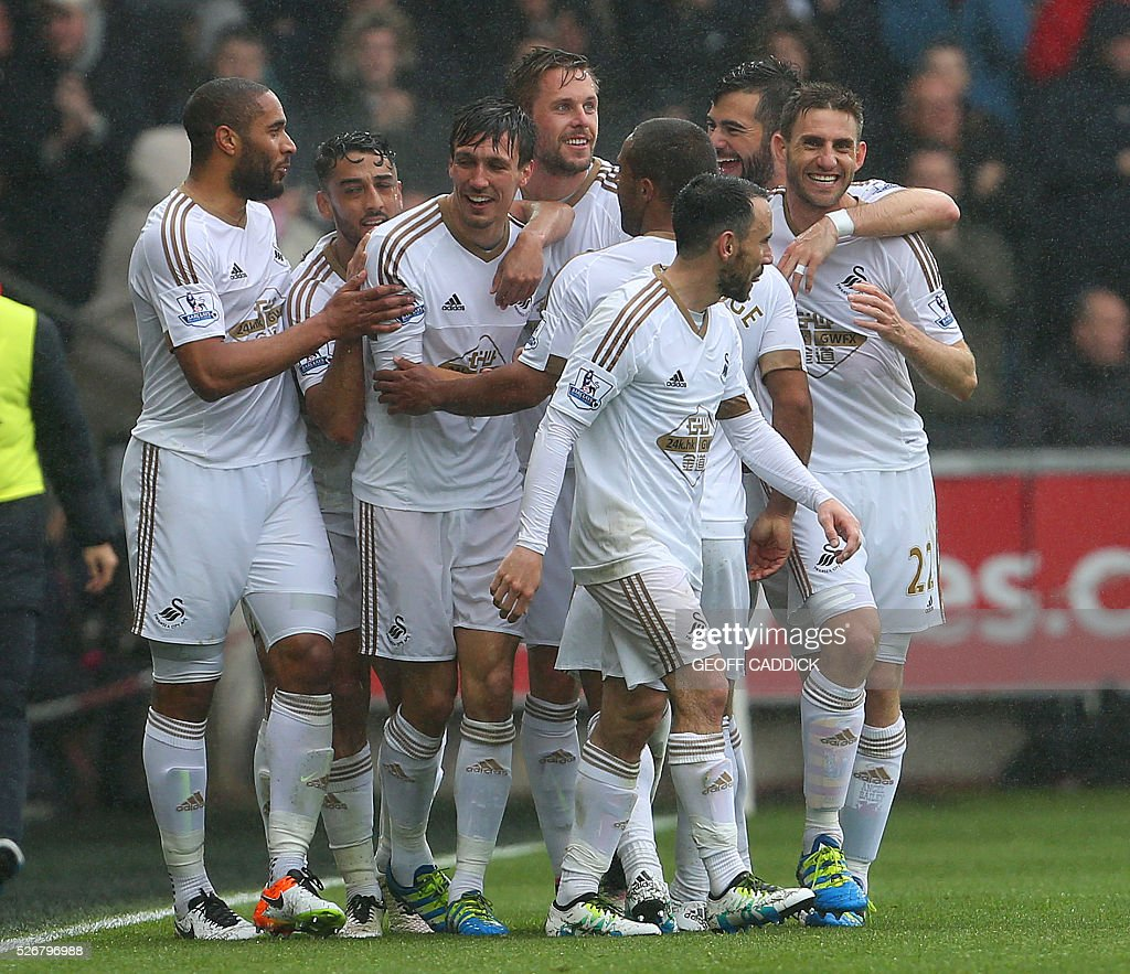 Swansea City's English midfielder Jack Cork (3L) celebrates with team-mates after scoring their second goal during the English Premier League football match between Swansea City and Liverpool FC at the Liberty Stadium, in Swansea, South Wales, on May 1, 2016. / AFP / GEOFF CADDICK / RESTRICTED TO EDITORIAL USE. No use with unauthorized audio, video, data, fixture lists, club/league logos or 'live' services. Online in-match use limited to 75 images, no video emulation. No use in betting, games or single club/league/player publications. /