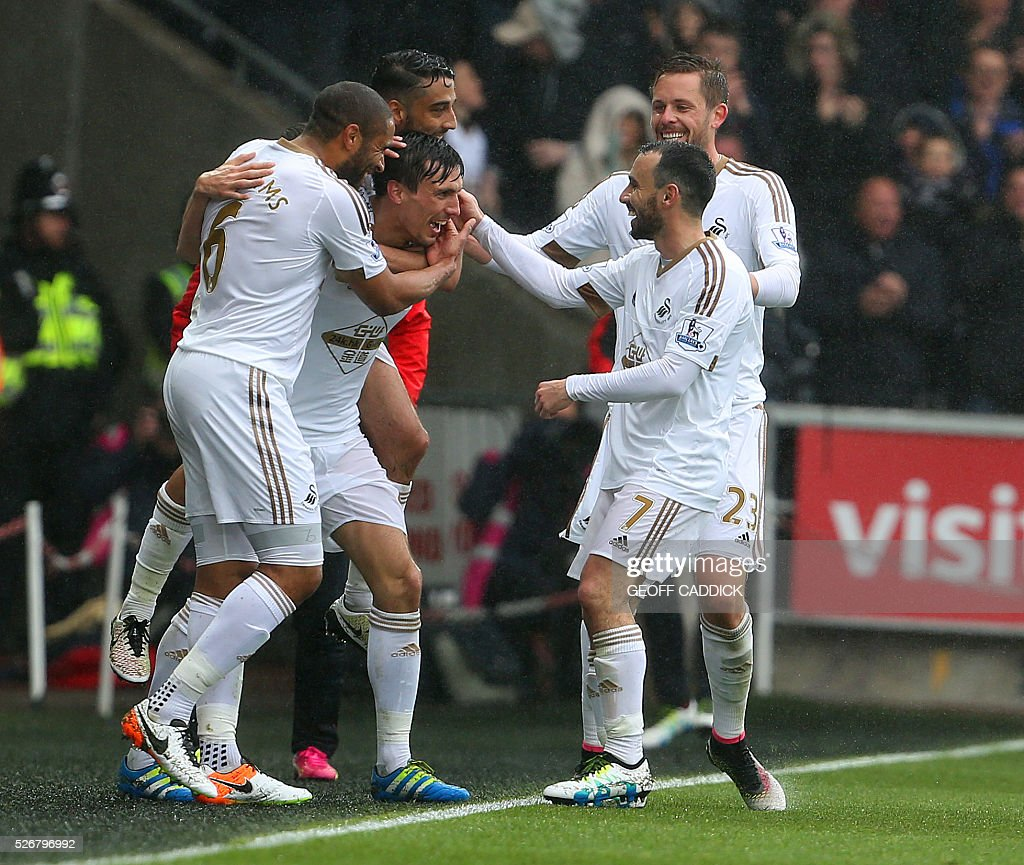 Swansea City's English midfielder Jack Cork (2L) celebrates with team-mates after scoring their second goal during the English Premier League football match between Swansea City and Liverpool FC at the Liberty Stadium, in Swansea, South Wales, on May 1, 2016. / AFP / GEOFF CADDICK / RESTRICTED TO EDITORIAL USE. No use with unauthorized audio, video, data, fixture lists, club/league logos or 'live' services. Online in-match use limited to 75 images, no video emulation. No use in betting, games or single club/league/player publications. /