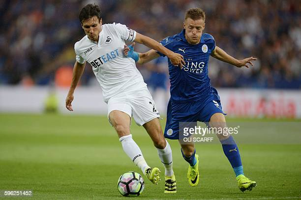 Swansea City's English midfielder Jack Cork vies with Leicester City's English striker Jamie Vardy during the English Premier League football match...