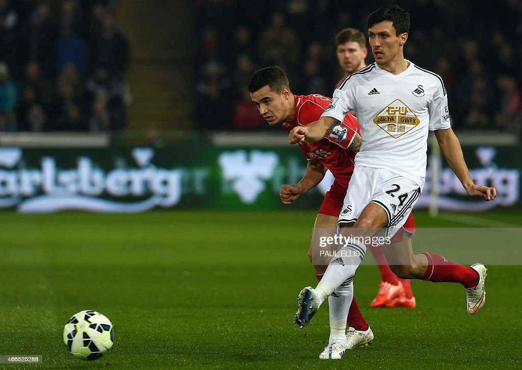 Swansea City's English midfielder <a gi-track='captionPersonalityLinkClicked' href=/galleries/search?phrase=Jack+Cork+-+Soccer+Player&family=editorial&specificpeople=4206991 ng-click='$event.stopPropagation()'>Jack Cork</a> (R) vies with Liverpool's Brazilian midfielder <a gi-track='captionPersonalityLinkClicked' href=/galleries/search?phrase=Philippe+Coutinho&family=editorial&specificpeople=6735575 ng-click='$event.stopPropagation()'>Philippe Coutinho</a> (L) during the English Premier League football match between Swansea City and Liverpool at the Liberty Stadium in Swansea, south Wales on March 16, 2015.