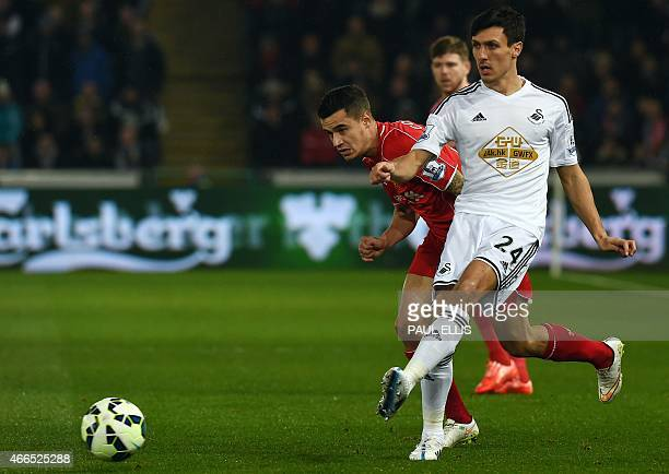 Swansea City's English midfielder Jack Cork vies with Liverpool's Brazilian midfielder Philippe Coutinho during the English Premier League football...