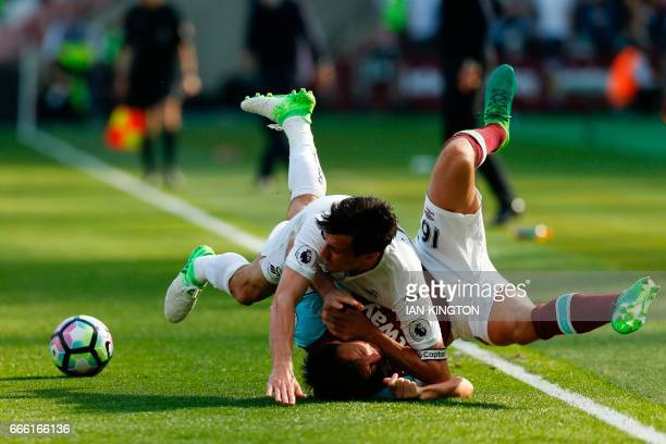 Swansea City's English midfielder Jack Cork vies with West Ham United's English midfielder Mark Noble during the English Premier League football...