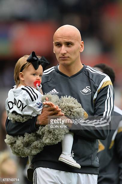Swansea City's English midfielder Jonjo Shelvey carries his daughter Lola Fleur after the final whistle in the English Premier League football match...