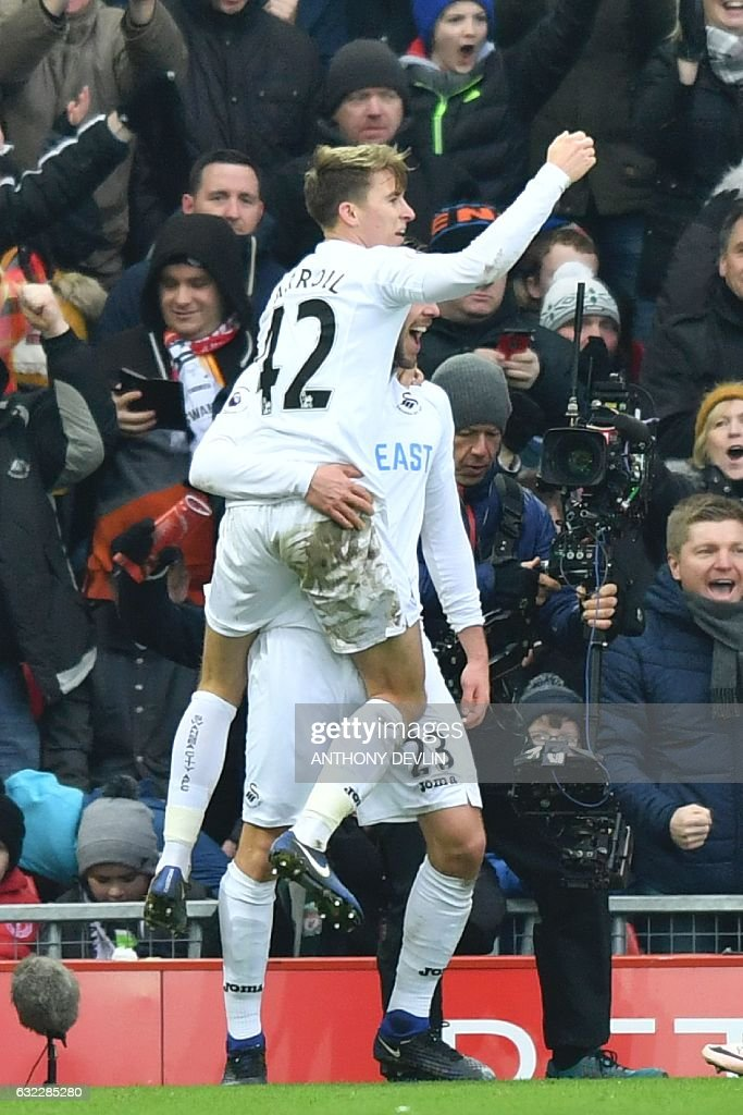 Swansea City's English midfielder Tom Carroll (L) celebrates in the arms of Swansea City's Icelandic midfielder Gylfi Sigurdsson (R) after Sigurdsson scored their third goal reacts after Swansea scored their third goal during the English Premier League football match between Liverpool and Swansea City at Anfield in Liverpool, north west England on January 21, 2017. / AFP / Anthony DEVLIN / RESTRICTED TO EDITORIAL USE. No use with unauthorized audio, video, data, fixture lists, club/league logos or 'live' services. Online in-match use limited to 75 images, no video emulation. No use in betting, games or single club/league/player publications. /