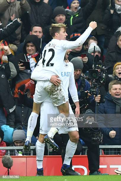 Swansea City's English midfielder Tom Carroll celebrates in the arms of Swansea City's Icelandic midfielder Gylfi Sigurdsson after Sigurdsson scored...