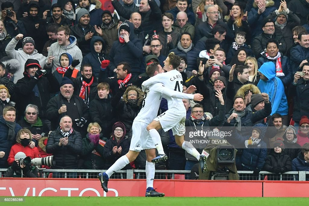 Swansea City's English midfielder Tom Carroll (R) jumps into the arms of Swansea City's Icelandic midfielder Gylfi Sigurdsson (L) after Sigurdsson scored their third goal reacts after Swansea scored their third goal during the English Premier League football match between Liverpool and Swansea City at Anfield in Liverpool, north west England on January 21, 2017. / AFP / Anthony DEVLIN / RESTRICTED TO EDITORIAL USE. No use with unauthorized audio, video, data, fixture lists, club/league logos or 'live' services. Online in-match use limited to 75 images, no video emulation. No use in betting, games or single club/league/player publications. /