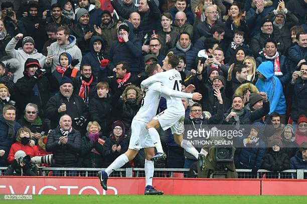 Swansea City's English midfielder Tom Carroll jumps into the arms of Swansea City's Icelandic midfielder Gylfi Sigurdsson after Sigurdsson scored...